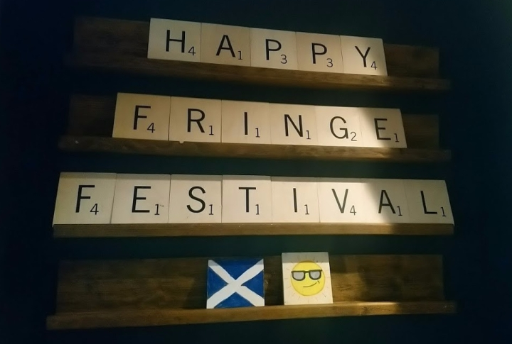 large scrabble letters spell out happy fringe festival on the wall