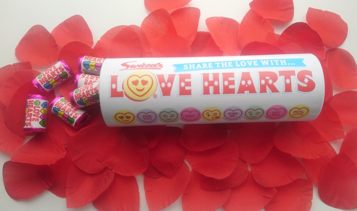 A tube of sweets on a bed of rose petals, with some packets of sweets pouring out.