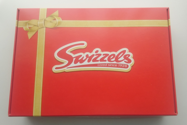 red box with printed ribbon and bow that bears the Swizzels logo.